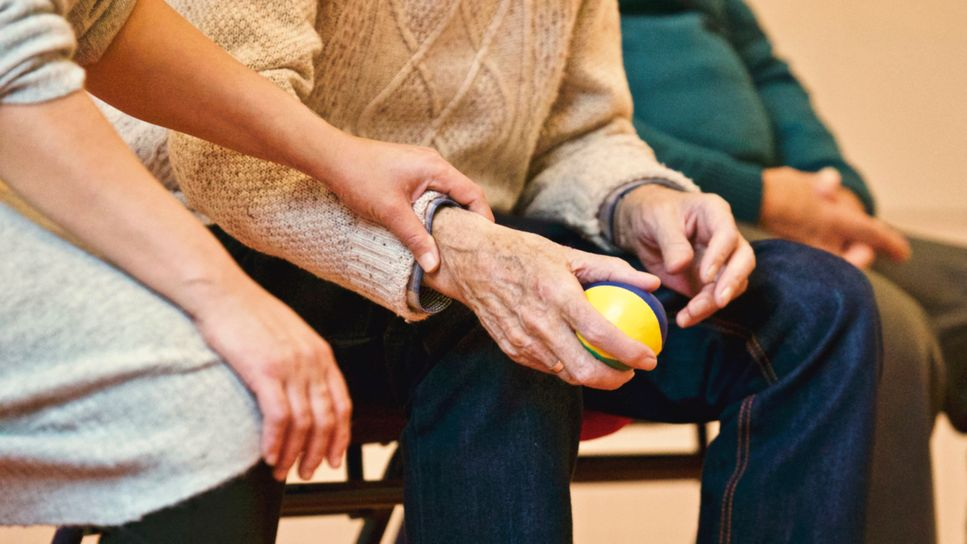 Small ball in elderly person hand